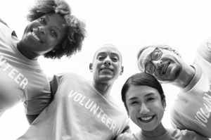 grayscale photography of group of people wearing volunteer printed shirt
