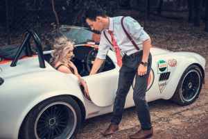 man standing beside convertible