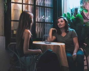 two women sitting and chatting near table