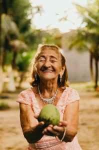 woman wearing pink dress holding fruit