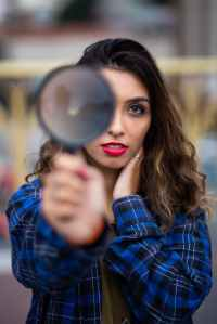 photo of woman holding magnifying glass
