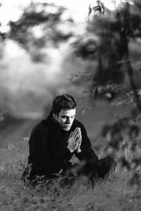 grayscale photography of man sitting on grass field