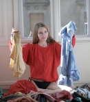 woman in red long sleeve shirt holding her clothes