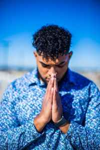 standing man in blue dress shirt praying