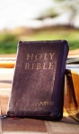 photo of holy bible near acoustic guitar