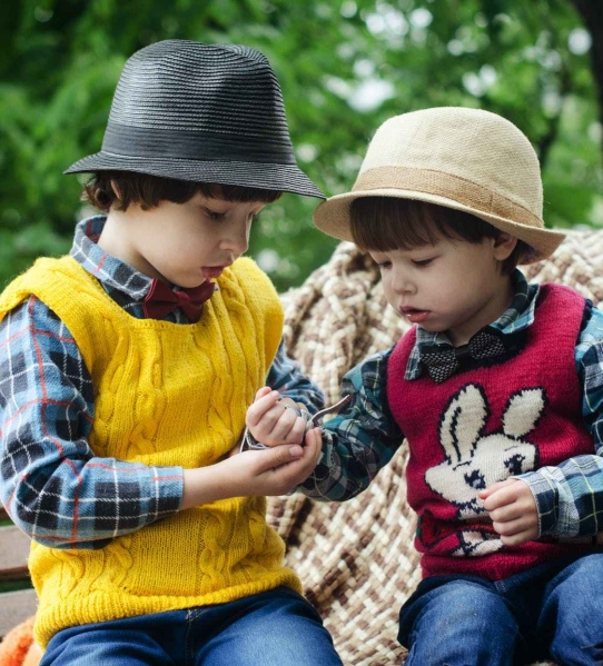 two boys sitting on bench wearing hats and long sleeved shirts
