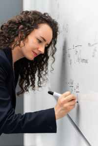 woman writing formula on whiteboard