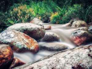 time lapse photo of river flowing on rocks