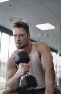 muscular athletic man exercising with dumbbell in sports center